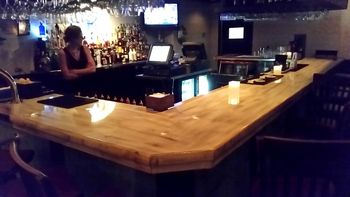 The Bar Area Was Off To The Right Of The Hostess Area. The Bar Top Was A  Thick Fitted Wood Slab With Multiple Coats Of Clear Lacquer.